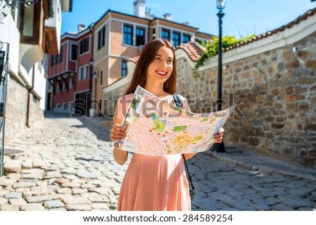Young woman traveling with map in Plovdiv old city center in Bulgaria - stock photo