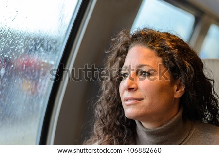 Young woman travelling on a train on a rainy day sitting looking out off the windows at the weather with a pensive expression - stock photo