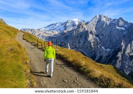 Young woman trekker walking mountains trail path near Marmolada glacier area, Dolomiti Mountains, italy  - stock photo