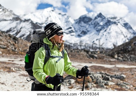 Young woman trekking in Himalaya Mountains, Nepal. Sport and fitness in autumn nature. Travel and trekking destination for tourists and trekkers - stock photo