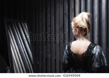 Young woman tries on dress standing in front of mirror - stock photo