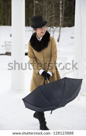 Young woman try close black umbrella on walk