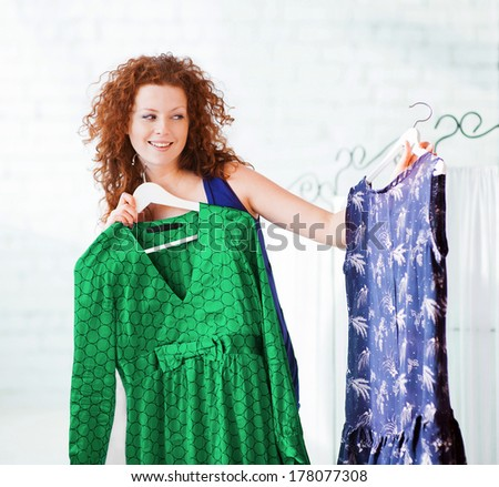 Young woman trying clothing dress - stock photo
