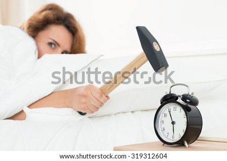 Young woman trying to break the alarm with hammer. Early morning waking up. - stock photo