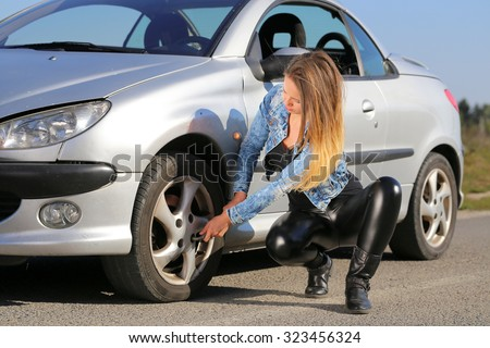 young woman trying to change wheel on the road - stock photo