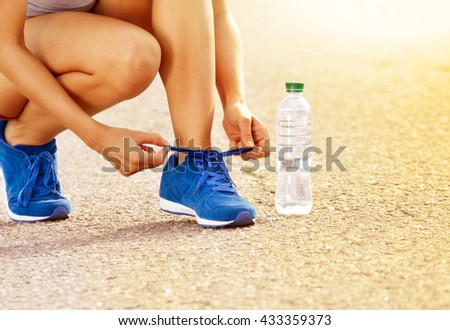 Young woman trying to lace up her sneakers