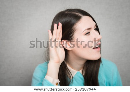 Young woman trying to listen something - stock photo