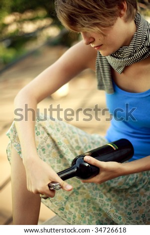 Young woman trying to open wine bottle