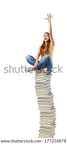 young woman trying to reach something sitting on a books tower - stock photo