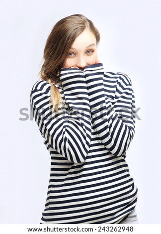 Young woman  tucking herself in  striped  sweater - stock photo