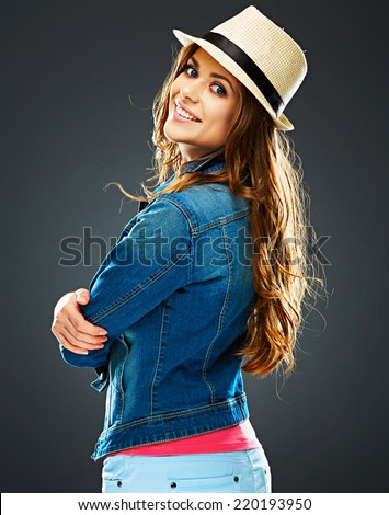 young woman turned and looking over his shoulder . smiling woman portrait standing back. - stock photo