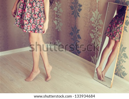 young woman turns the mirror - stock photo