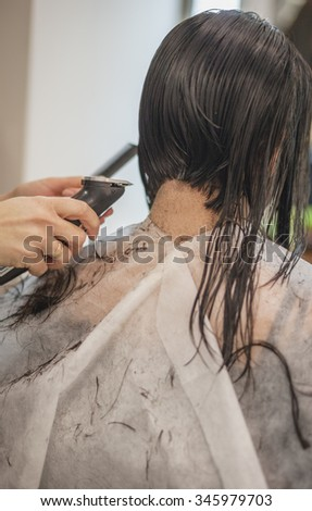 Young woman, TWENTY five, getting hair cut, rear view.