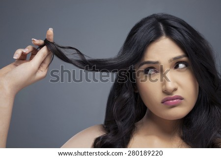 Young woman twisting hair finger over colored background - stock photo