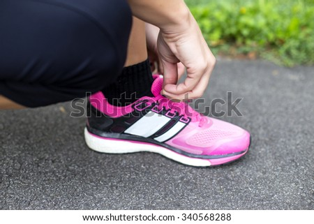 Young woman tying shoelaces