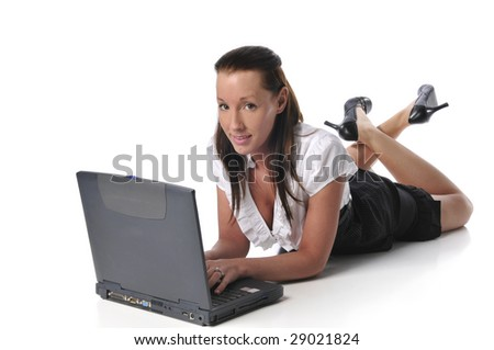 Young woman typing on a laptop and lying on the ground