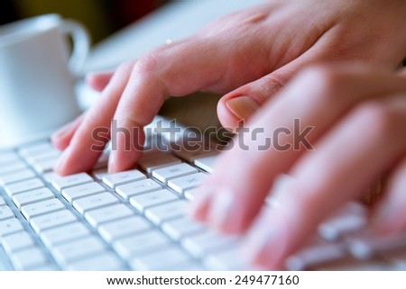Young woman typing on a white modern computer keyboard while having a coffee on the side. Soft focus detail. Modern, business,finance, computer, technology, hacking and job hunting concept. High key. - stock photo
