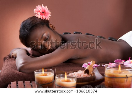 Young woman undergoing lastone therapy at beauty spa - stock photo