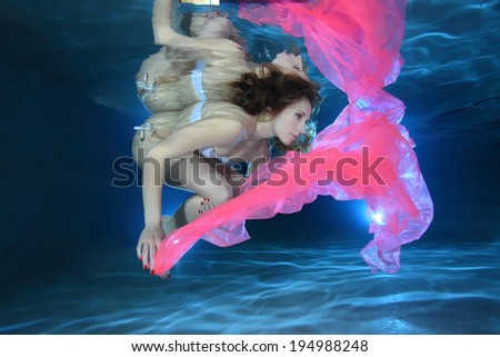 Young woman underwater in the pool floating with pink foulard  - stock photo