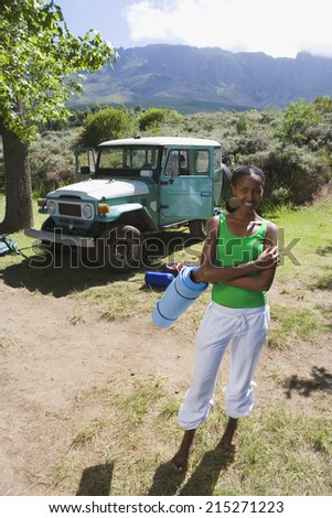 Young woman unloading parked jeep at start of camping holiday, holding sleeping mat, smiling, portrait