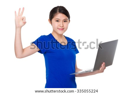 Young woman use of the notebook computer and ok sign gesture