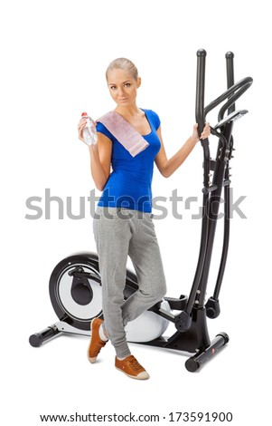Young woman uses elliptical cross trainer. - stock photo