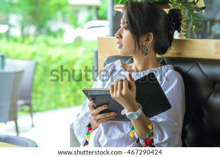 Young woman uses tablet being looking outside green nature while relaxing at home with coffee on the sofa couch