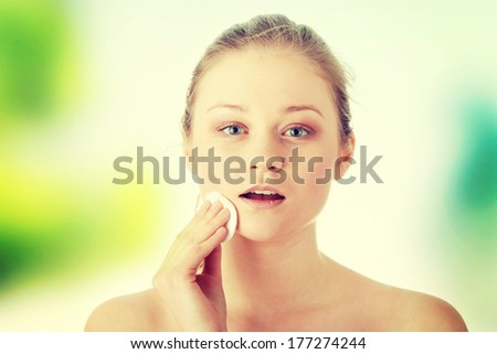 Young woman using a cotton pad to remove her make-up  - stock photo