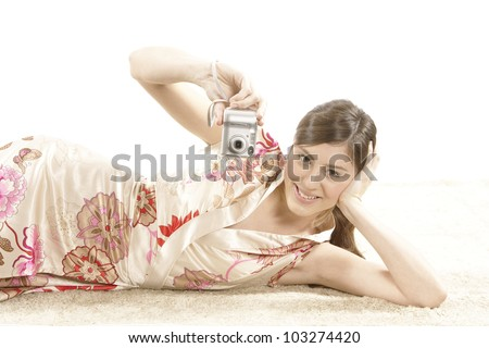 Young woman using a digital photo camera while laying down on a carpet. - stock photo