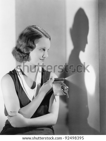 Young woman using a flashlight on her key chain