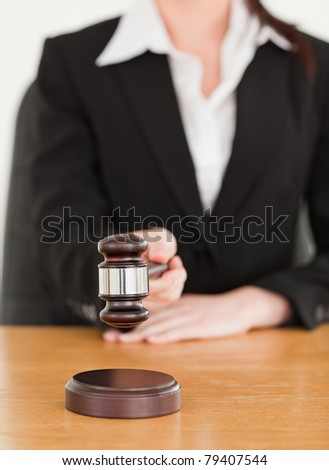 Young woman using a gavel while sitting at a desk against a white background - stock photo