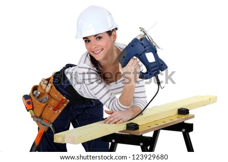 Young woman using a jigsaw - stock photo