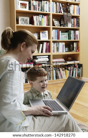 Young woman using a laptop with her son
