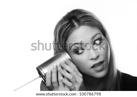 Young woman using a metal tin as a telephone - stock photo