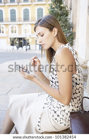 Young woman using a smart phone in a European city. - stock photo