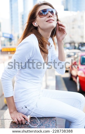 Young woman using a smart phone outdoors / photography of young Caucasian woman wearing sunglasses  - stock photo