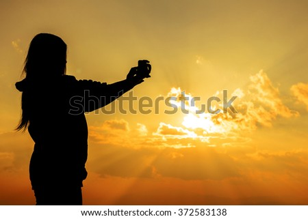 young woman using a smart phone  silhouette at sunset