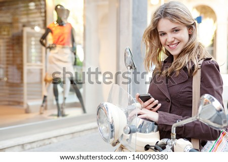 Young woman using a smartphone while standing by her motorbike in the shopping district of a city, with a fashion store window with manikins in the background. - stock photo
