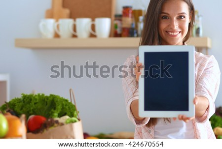 Young woman using a tablet computer to cook in her kitchen - stock photo