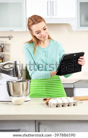 Young woman using a tablet computer to follow a recipe - stock photo