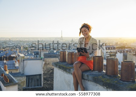 Young woman using a tablet pc on the roofs of Paris