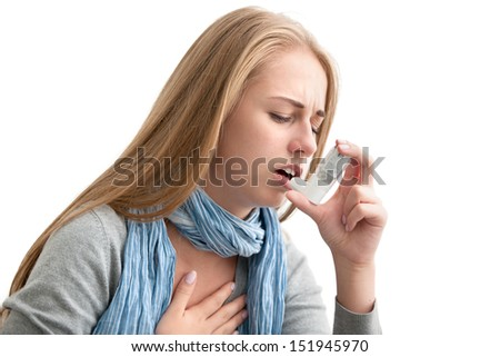 Young woman using an asthma inhaler as prevention - stock photo