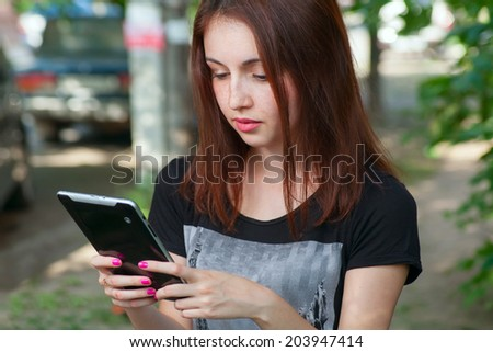 Young woman using app on a talet PC or smart phone. Female student with tablet modile education - stock photo