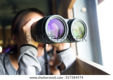 Young woman using binoculars for birdwatching - stock photo