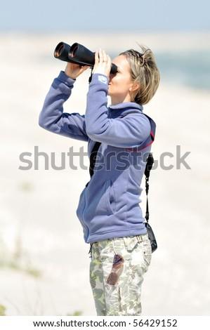 young woman using binoculars outdoor - stock photo