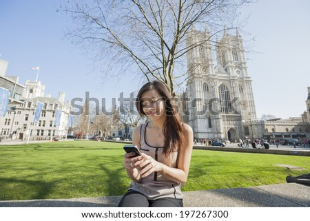 Young woman using cell phone against Westminster Abbey in London; England; UK - stock photo