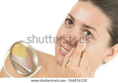 Young woman using concealer looking in the mirror - stock photo