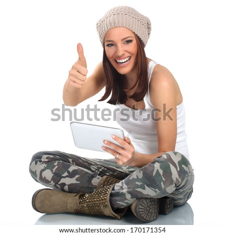 Young woman using digital tablet and holding thumb up