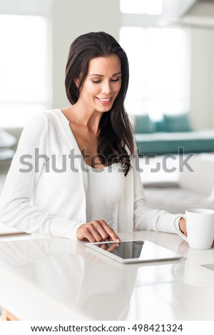 Young woman using digital tablet computer in modern home interior