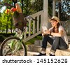 Young woman using digital tablet next to her bicycle. - stock photo